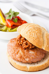 A small gourmet hamburger with side dish and Bolognese sauce