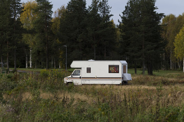 A parked camper on a field with some trees in the background