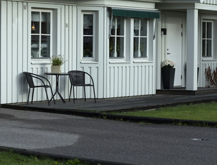 Outside of a house with some chairs and a table