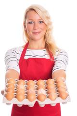 Frau mit Schürze trägt eine Pappe mit rohen Eiern