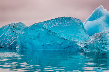 Blue iceberg just after flipping in water, Iceland