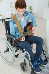 Handicapped teenager playing the guitar