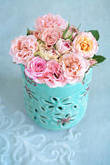 Delicate pink roses in a blue vase on the table.
