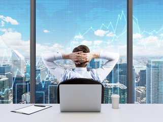 Rear view of the relaxing businessman with crossed hands behind his head, who is looking at NYC. Modern Panoramic office or work place with New York city view. Financial charts are over the windows.