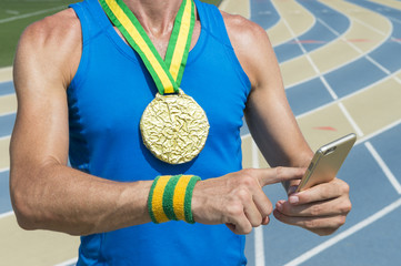 Gold medal athlete standing at running track using his mobile phone