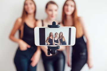 Beautiful young girls taking a photo with selfie stick