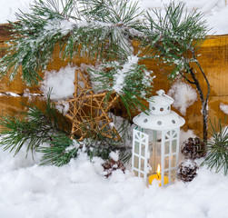 Decorative lantern burning in the snow with a conifer branch