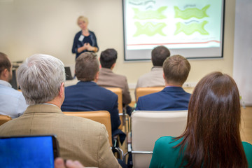 Rear View of Office Employees in a Business Meeting Inside the Office, Listening to Woman Presenting Something. Wall mural