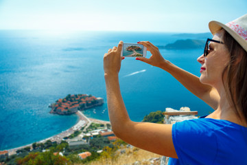 Girl  making photos by the smartphone island of Sveti Stefan, Mo
