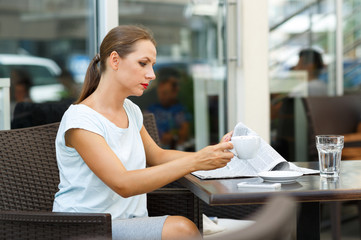 Attractive woman reading a newspaper and drinking morning coffee