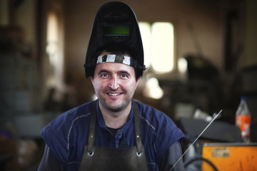 Photo of recognizable young man who working on as a welder. Dark and contrast background. Young and happy worker looking at the camera and smiling up. Visible noise.