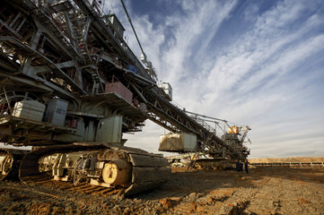 One side of huge mining drill machine photographed from a ground with wide angle lens. Dramatic and colorful sky in background.