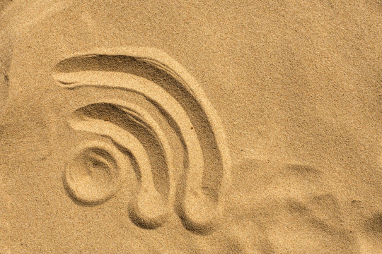 WiFi sign drafted in the sand on the beach