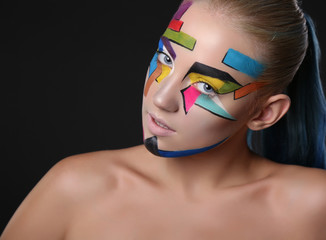 young girl with bright geometric pattern on her face.Halloween style
