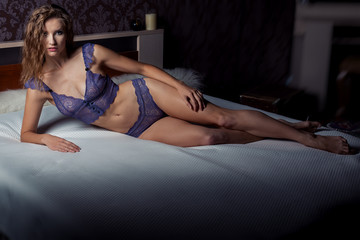 beautiful sexy slim young girl in purple lingerie in the bedroom lying on the bed in a dark room
