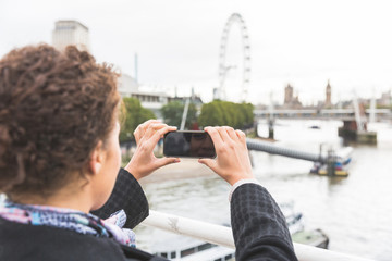 Young woman taking photo of Big Ben in London with her smart pho