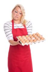 Frau hält eine Palette Eier und zieht eine Schnute