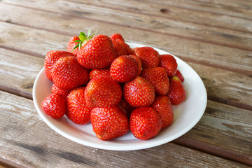 Strawberry plate on the wooden table