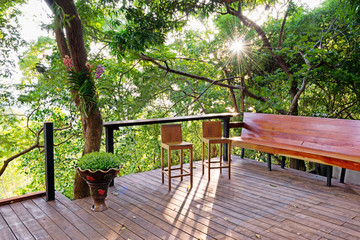 Wooden deck with benches and chair in the backyard
