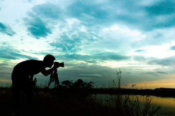 Silhouette of photographer taking pictures of sunset