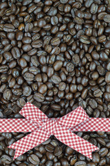 Red tartan ribbon on coffee beans background