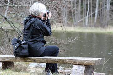 Woman photographer by a lake