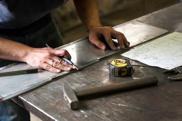 Metalworker marking measurements on metal Wall mural