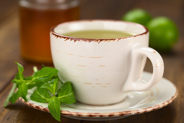 Freshly prepared mint tea out of fresh leaves served in a cup with leaves on the side and honey and lime in the back (Selective Focus, Focus on the front rim of the cup and the tip of the mint leaf)