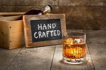 Hand crafted small batch craft liquor glass bourbon whisky scotch brandy rum on wooden rustic surface