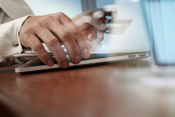 close up of hands using laptop and holding credit card as Online