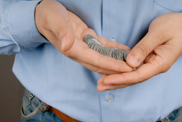 Males hand holding several coins