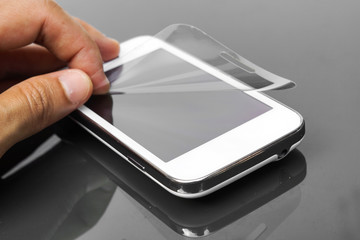 hand laying scratch protective film on a smartphone