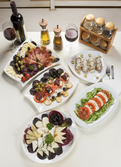 Five plates with appetizer, two glasses and a bottle of red wine, spice oil and jars with spices served on the table.