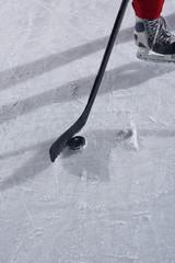 hockey sticsk and puck on ice