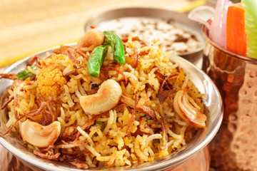 Vegetable Biryani, Indian cuisine accompanied with fresh slice of carrot, cucumber, onion and Raita garnished with fried beans,onion and cashew nuts