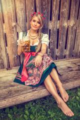 Pretty german oktoberfest blonde woman in a dirndl dress with beer