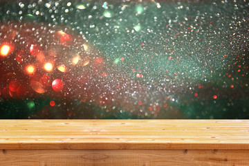 rustic wood table in front of glitter silver, green, blue and gold bright bokeh lights