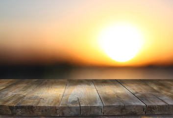 image of textured wood table in front of beach landscape at sunset time