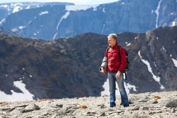 Mature Caucasian man hiking on the mountain plateau along, copy space
