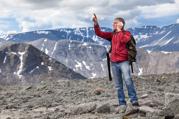 Mature Caucasian hiker a man shows to the mountain top, talking on a cell phone