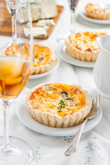 quiche with pumpkin and blue cheese. French cuisine. table set, plates, glasses with wine