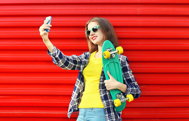Pretty cool young woman in sunglasses with skateboard taking pic