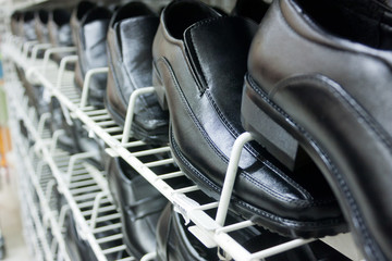 Black Leather Shoes On Shelves In Perspective View