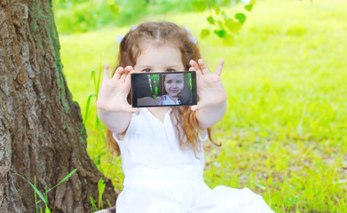 Child making self portrait on smartphone in summer park, screen