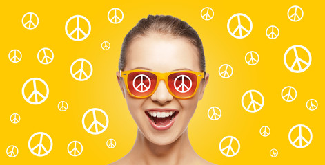 happy teenage hippy girl in shades with peace sign