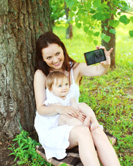 Happy smiling mom and baby taking self-portrait on smartphone si