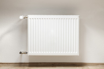 Heating radiator in a white room with laminated wooden floor