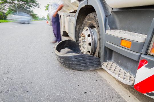 Damaged 18 wheeler semi truck burst tires by highway street, wit