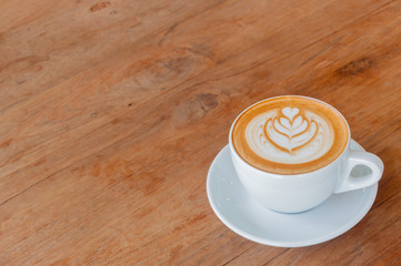 Hot cafe latte with latte art on wooden table