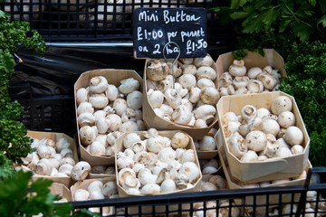 Mini button mushrooms for sale at a vegetable market